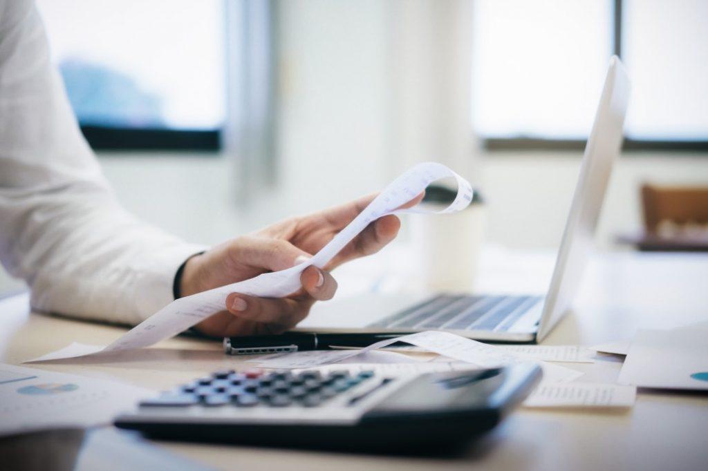 inadimplência na pandemia - pessoa segurando um papel, em uma mesa com calculadora e notebook