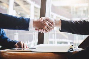 Fusões e aquisições - duas pessoas apertando as mãos
