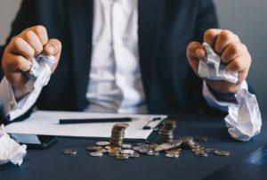 conflitos e os estímulos para aplicação na recuperação judicial e na falência - homem amassando bolinhas de papel com as mãos