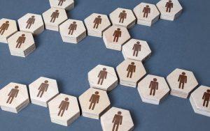 tipos societários - peças hexagonais de madeira com figuras humanas desenhadas