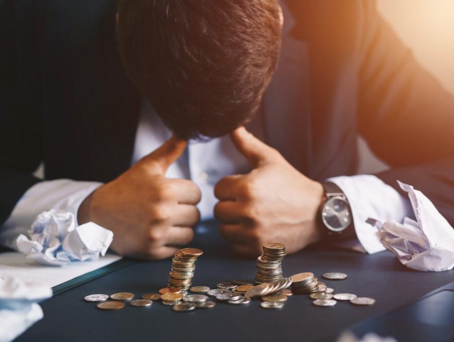 dip financing recuperação judicial - homem frustrado com a cabeça encostada na mesa